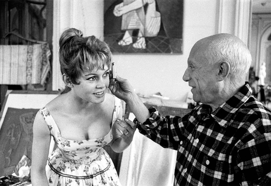 Picasso checking Brigitte Bardot's face with a light meter during the Cannes Film Festival, 1956